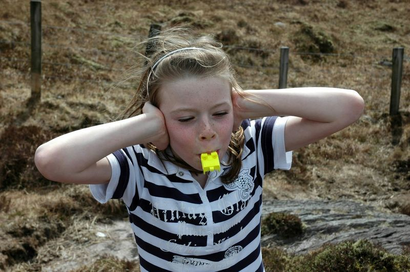 High angle view of girl blowing whistle standing on field