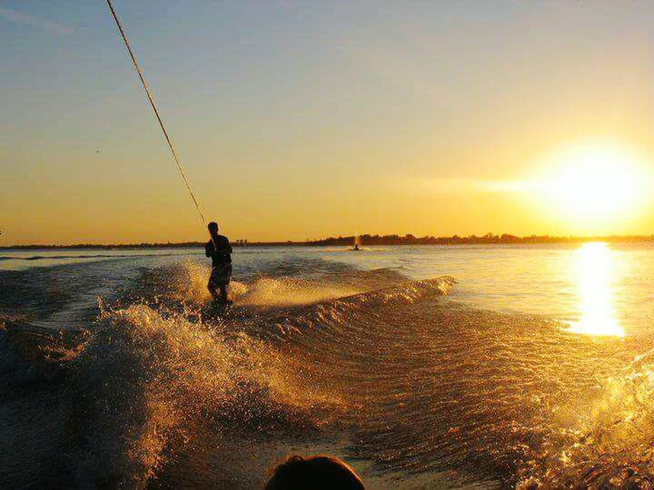 sunset, sea, one person, fishing, real people, silhouette, water, nature, standing, leisure activity, weekend activities, men, outdoors, holding, beauty in nature, sky, sun, vacations, sunlight, sport, fishing pole, horizon over water, scenics, extreme sports, lifestyles, adventure, one man only, wave, day, people