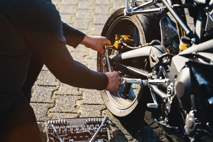 Midsection of mechanic repairing motorcycle on street