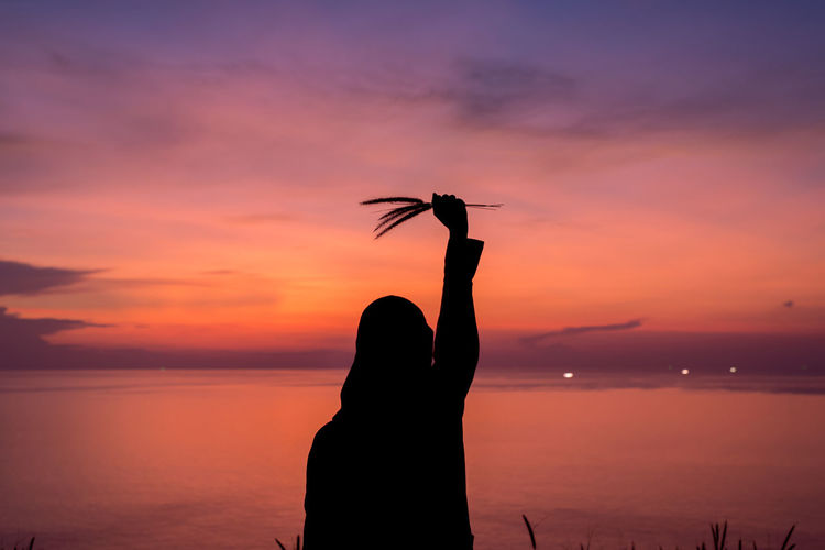 Rear view of silhouette woman holding plants while standing by sea against sky during sunset