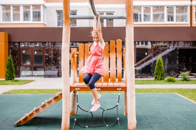 Full length of girl playing in park near building