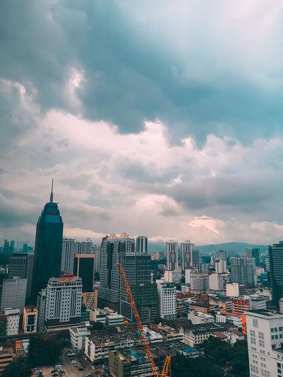 Modern buildings in city against cloudy sky