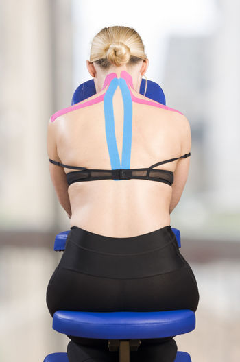 Rear view of mature woman with pink kinesio tape sitting on neck massage chair