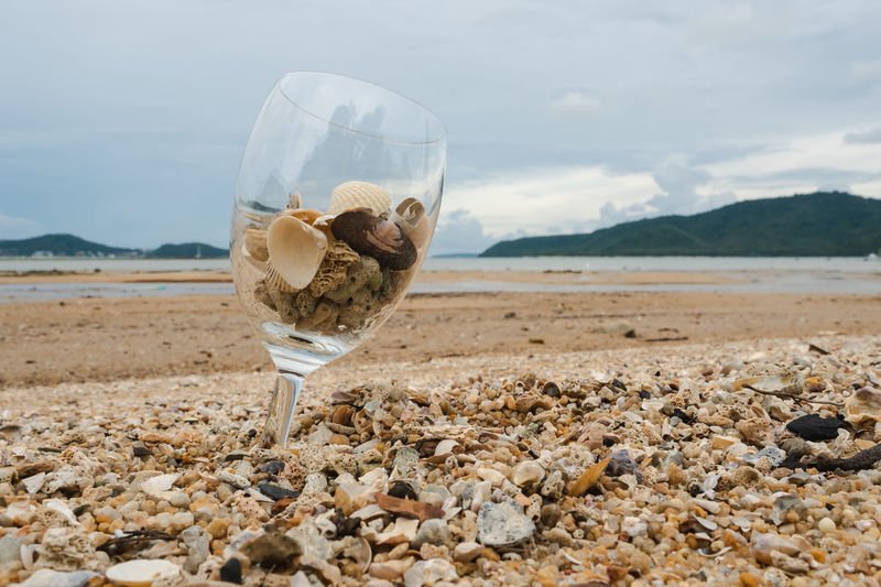 Drinking glass on beach by sea against sky