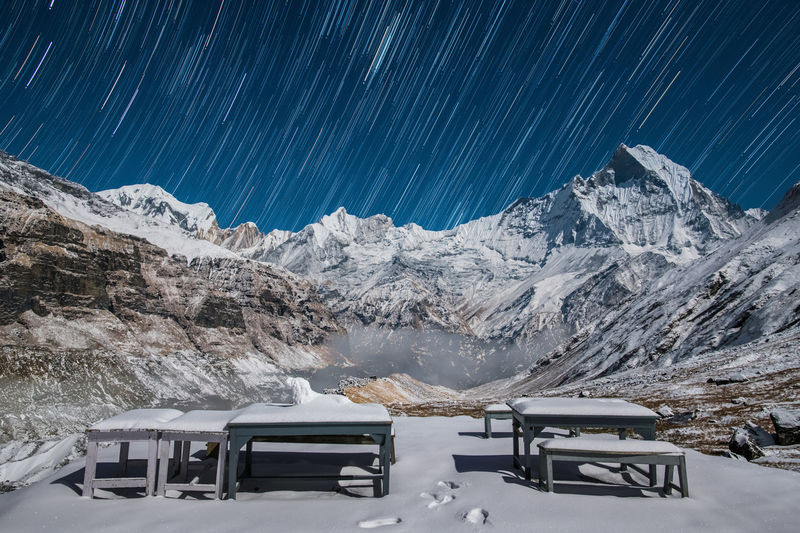 Snowcapped mountains against star trails
