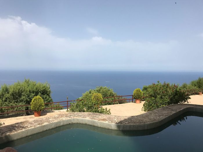 Scenic view of swimming pool by sea against sky