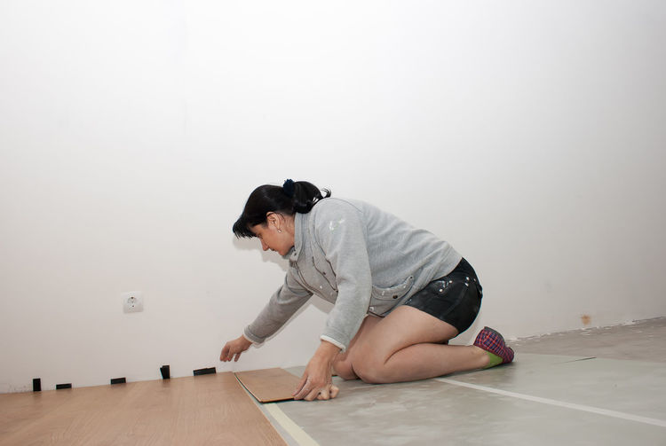 Woman Adjusting Planks On Floor At Home
