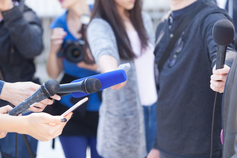 Journalists holding microphones, conducting media interview. News conference. Media Event Interview Journalist Press Broadcast Broadcasting Comment Communication Conference Correspondent Holding Information Journalism Microphone News People Public; Question Report Reporter; Television Television Tower