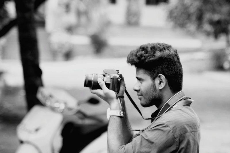Man photographing through camera outdoors