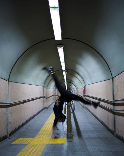 Side View Of Woman Practicing Handstand At Subway Station