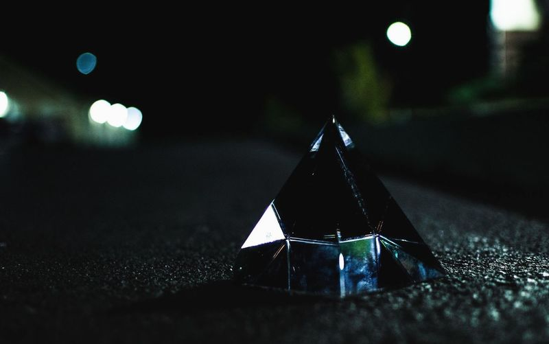 Pyramid shape crystal on road at night
