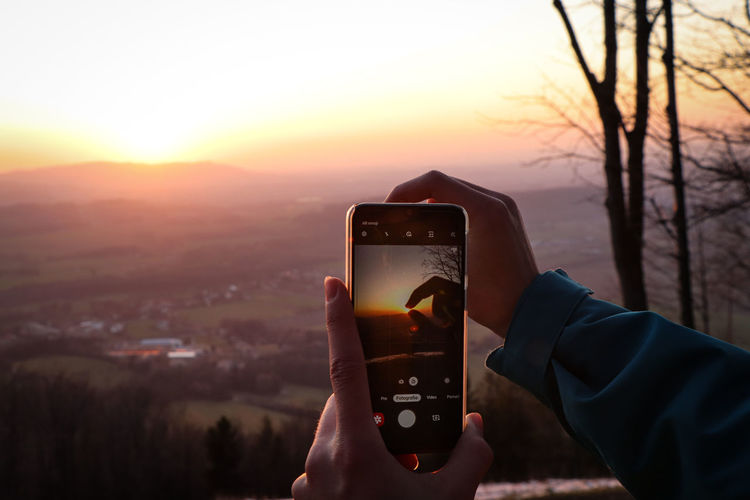 Man photographing using smart phone against sky during sunset