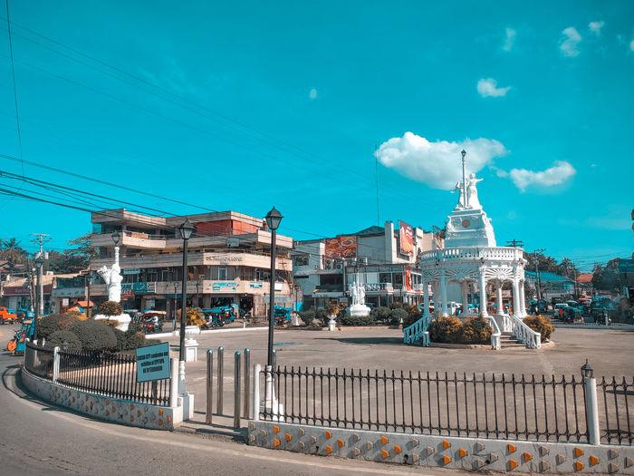 Road by buildings against blue sky