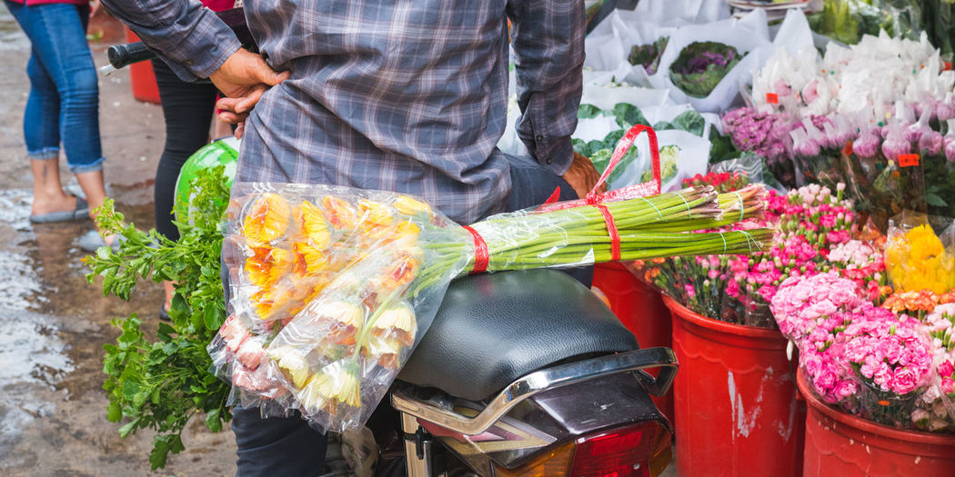 Midsection of man selling flowers