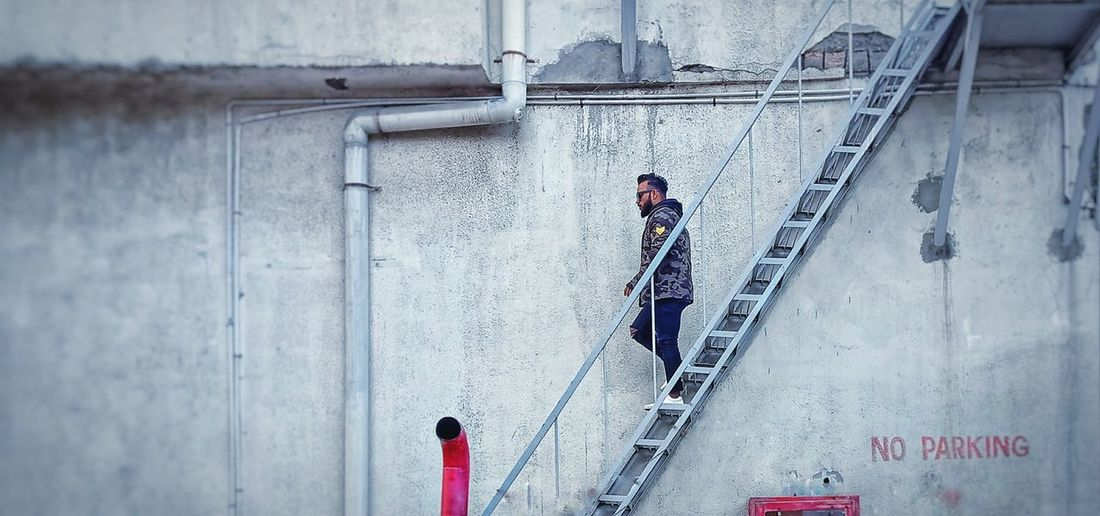 Full Length Of Man Walking On Staircase By Wall