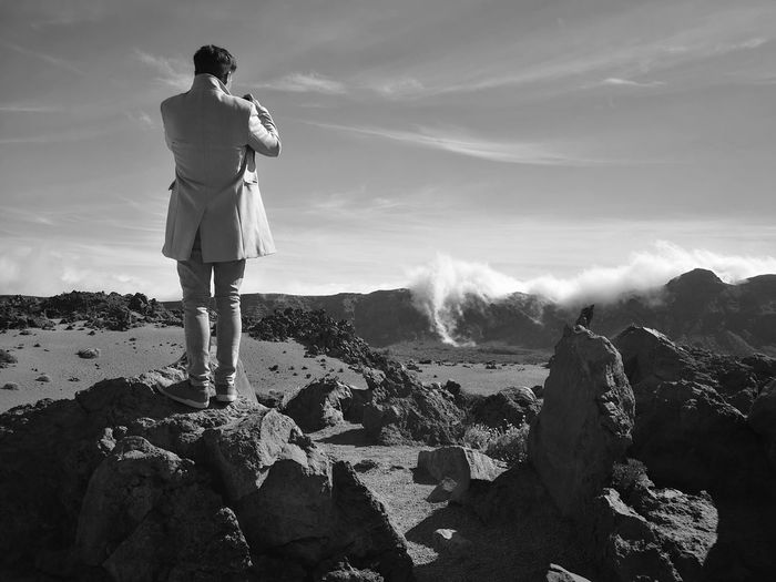 Rear view of young man standing on rock against sky