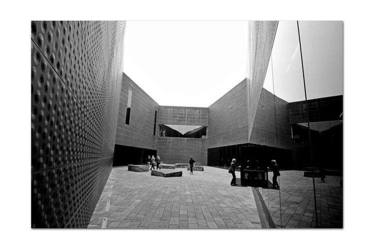 All About Angles 8 DeYoung Museum Courtyard  Entrance Fine Arts Museum Golden Gate Park Bnw_corner Bnw_friday_eyeemchallenge Architecture Architectural Detail Perforated & Dimpled Copper Plates Façade Drawn Stones Seating Monochrome_Photography Monochrome Black & White Black & White Photography Black And White Black And White Collection  Reflection Smoke Tinted Glass Doorway New Museum Opened 2005 Replaced 1895 Original Building Damaged By 1989 Loma Prieta Earthquake People Walking  Building Exterior Entryway The Architect - 2018 EyeEm Awards