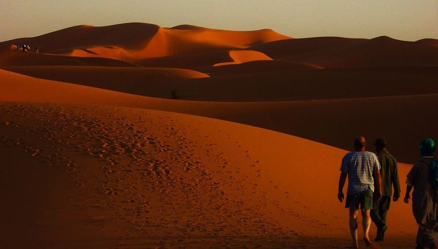 Rear view of people on desert against sky during sunset