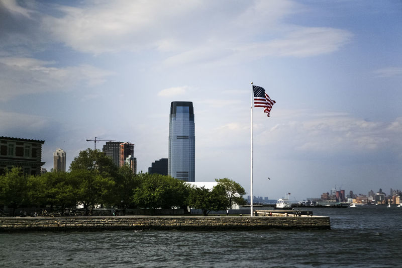 Hudson River By American Flag And Buildings Against Sky