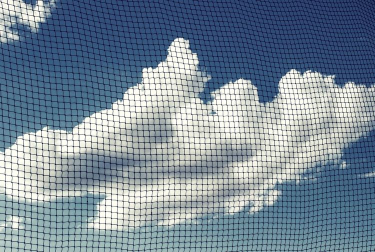 Low angle view of cloudy sky seen through netting