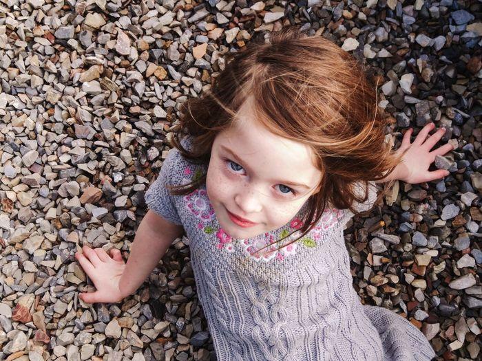 Portrait Of Cute Girl Lying On Pebbles
