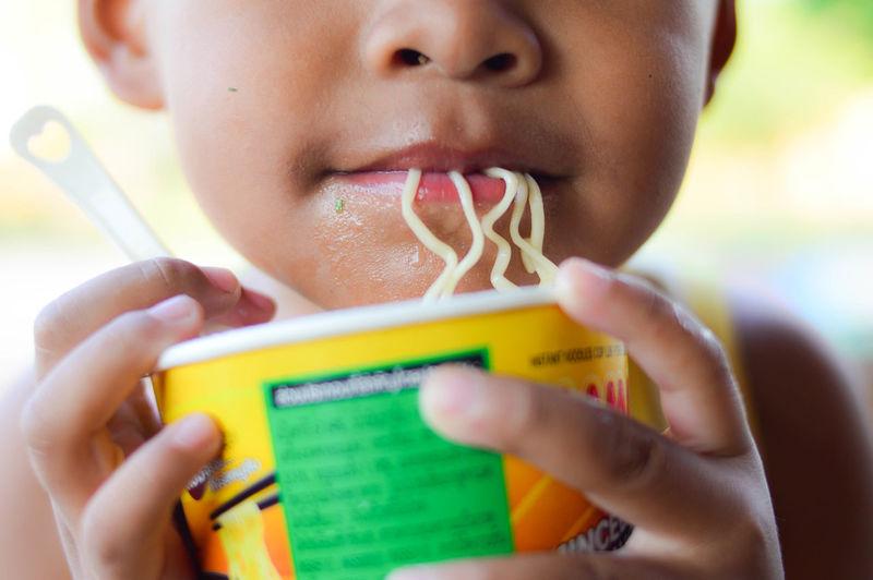 Close-up portrait of boy holding instant noodles cup