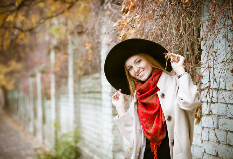 Portrait of smiling young woman standing against tree
