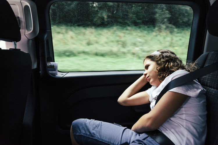 Bored Girl Looking Through Window While Sitting In Car