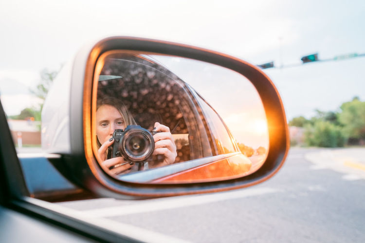 Portrait of woman photographing car on side-view mirror