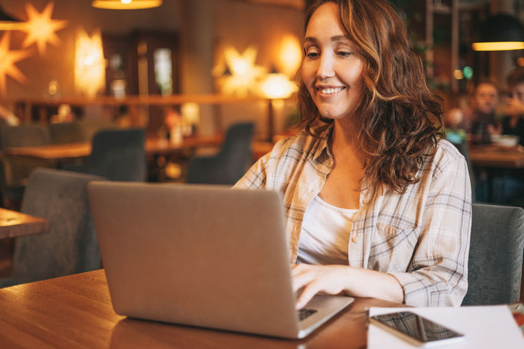 Adult charming brunette woman in plaid shirt working with laptop at cafe