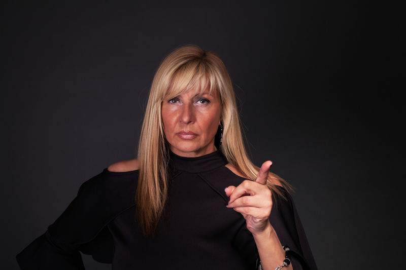 Serious woman raising her finger Adult Beautiful Woman Black Background Blond Hair Boss Business Business Finance And Industry Discipline Forbidding Lady Mature Adult Mature Women Middle-aged Mother One Person One Woman Only Parents People Person Serious Studio Shot Woman Woman Portrait