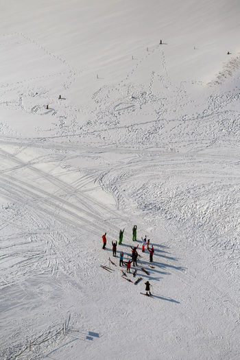 High angle view of excited hikers standing with arms raised on snow