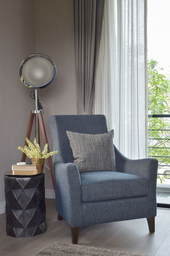 Electric lamp on armchair on floor