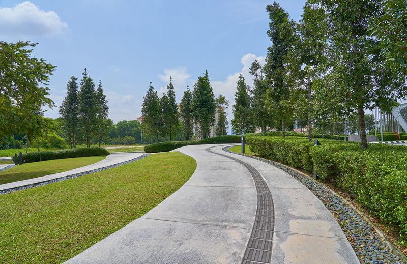 Footpath in park against sky in city