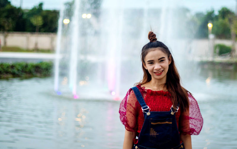 Portrait of smiling young woman standing against fountain