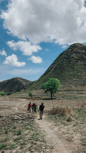 Rear view of people walking on mountain road
