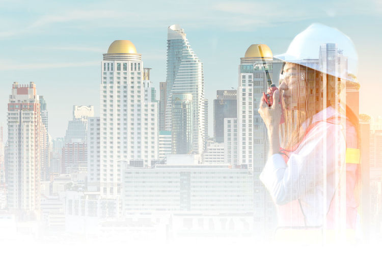 Digital composite image of woman and buildings against sky
