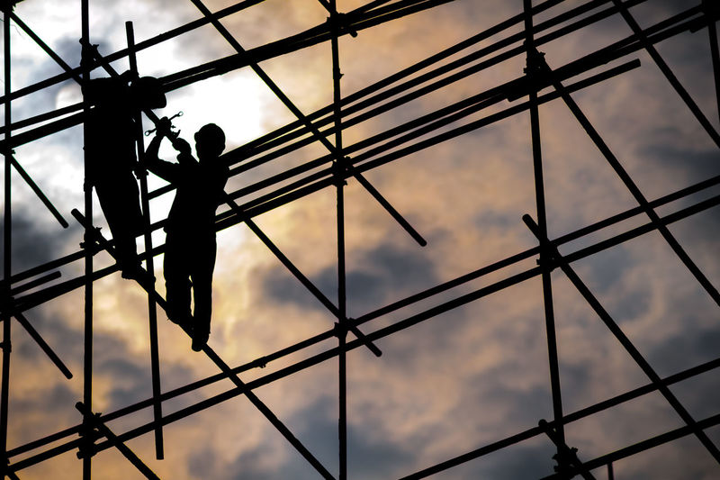 Low angle view worker standing on scaffolding against sky during sunset