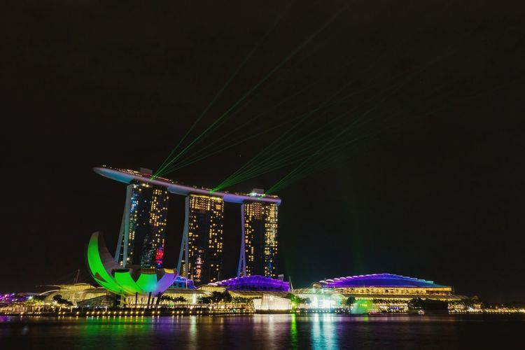 Illuminated Marina Bay Sands And Artscience Museum Against Clear Sky At Night