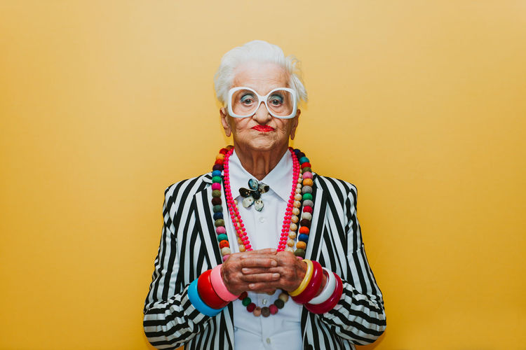 Portrait of stylish senior woman wearing colorful jewelry standing against yellow background