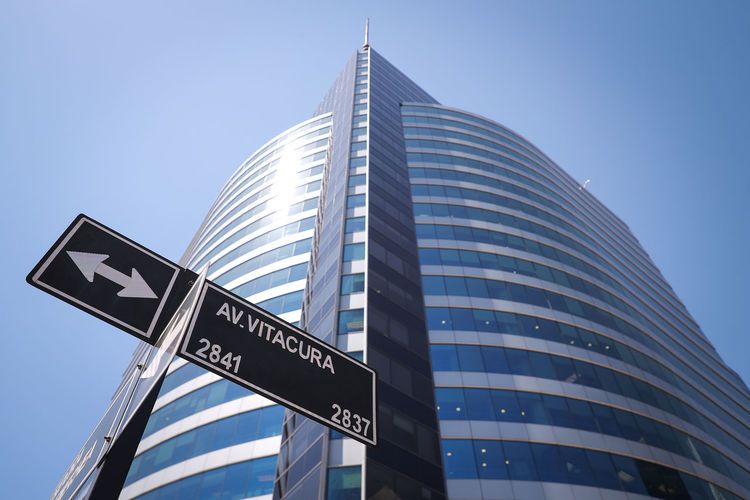 Low Angle View Building Exterior Sign Built Structure Text Communication Architecture Sky Guidance Road Sign City Symbol No People Western Script Directional Sign Office Building Exterior Day Building One Way Arrow Symbol Modern Skyscraper