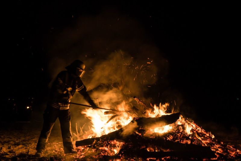 Firefighter against bonfire at night