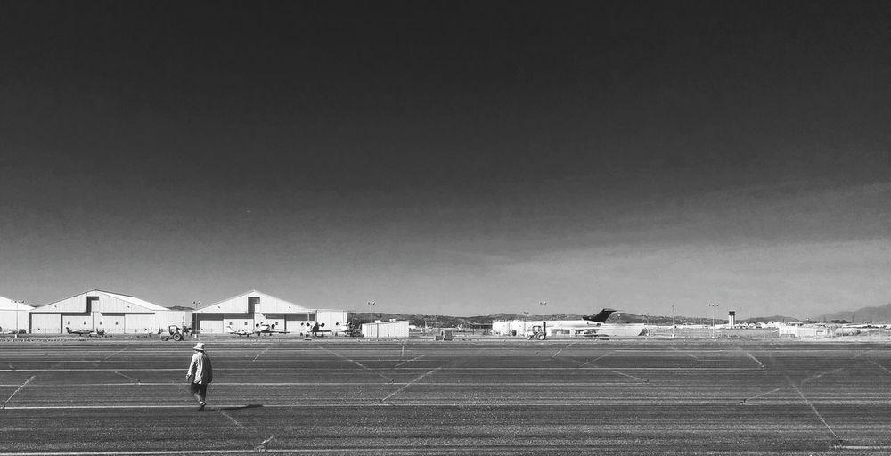 Rear view of man at airport runway against sky