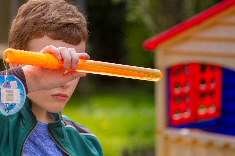 Close-Up Of Boy Holding Laser Sword
