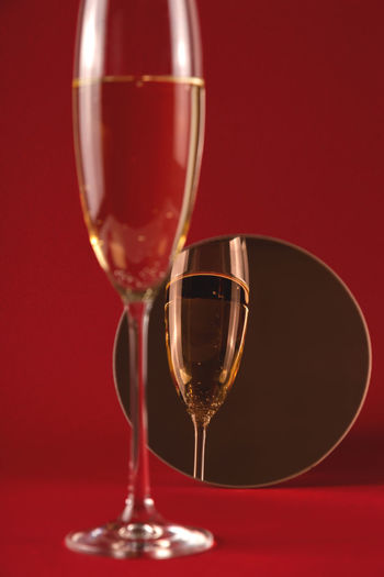 Glass of champagne with reflection in a small round mirror on a red background.