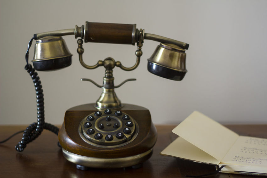 Vintage phone on wooden table and open phonebook on the side Antiquated Antique Classic Retro Analog Antique Call Communication Connection Dial Handset Landline Phone No People Nostalgia Number Old Old Telephone Phone Phonebook Retro Styled Revival Style Telecommunications Equipment Telephone Vintage