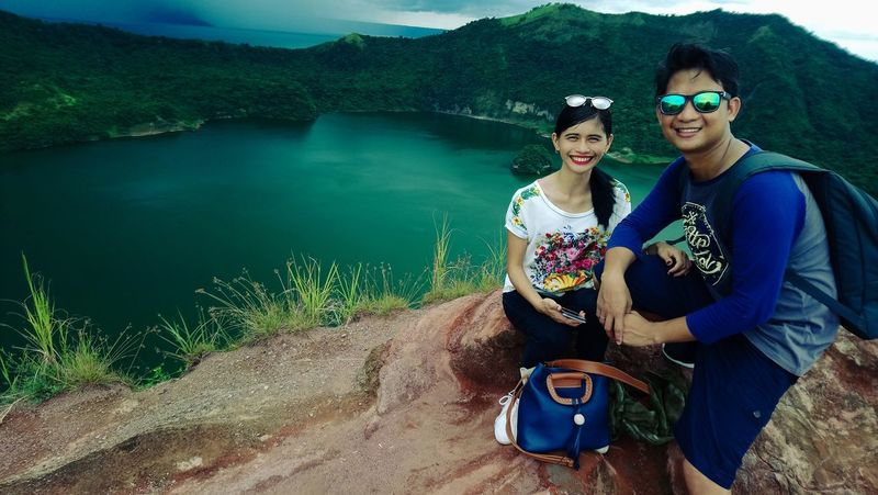 Crater of Taal Volcano Two People Togetherness Adventure Sitting People Lake Young Adult Smiling Portrait Men Women Day Happiness Couple - Relationship Looking At Camera Outdoors Laughter Active Volcano Small Volcano Mountain View Red Lava Crater Sky World Smallest Volcano Mountains Connected By Travel Second Acts EyeEmNewHere Perspectives On Nature Be. Ready. An Eye For Travel
