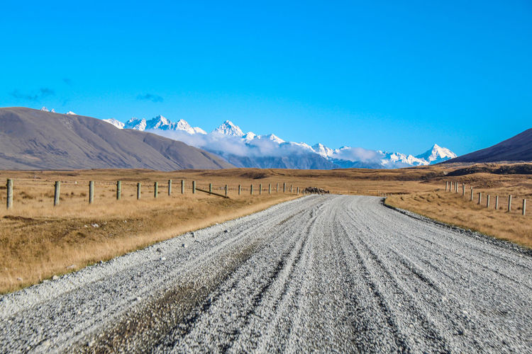 Scenic view of empty road by mountains against blue sky