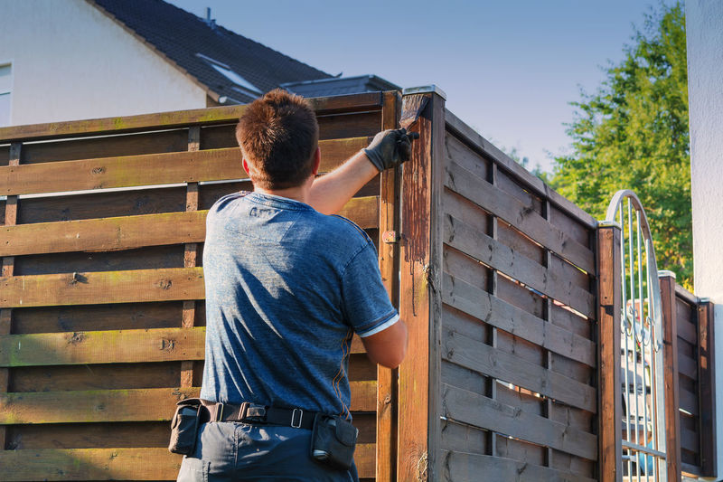 Man with artificial heart strokes a wood fence in the garden. Home Man Wood Adult Adults Only Casual Clothing Day Fence Garden Human Hand Manual Worker Men Occupation One Man Only One Person Only Men Outdoors People Rear View Repairing Wood - Material Work Tool Working Young Adult