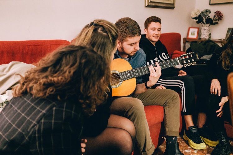 Full length of man playing guitar on sofa